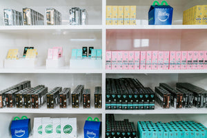Picture of various VVS vape products and accessories displayed on eight wall shelves.