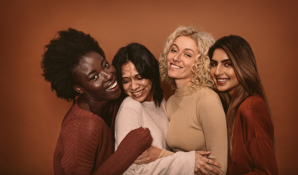 Women of diverse ethnicities and skin tones smiling and having fun