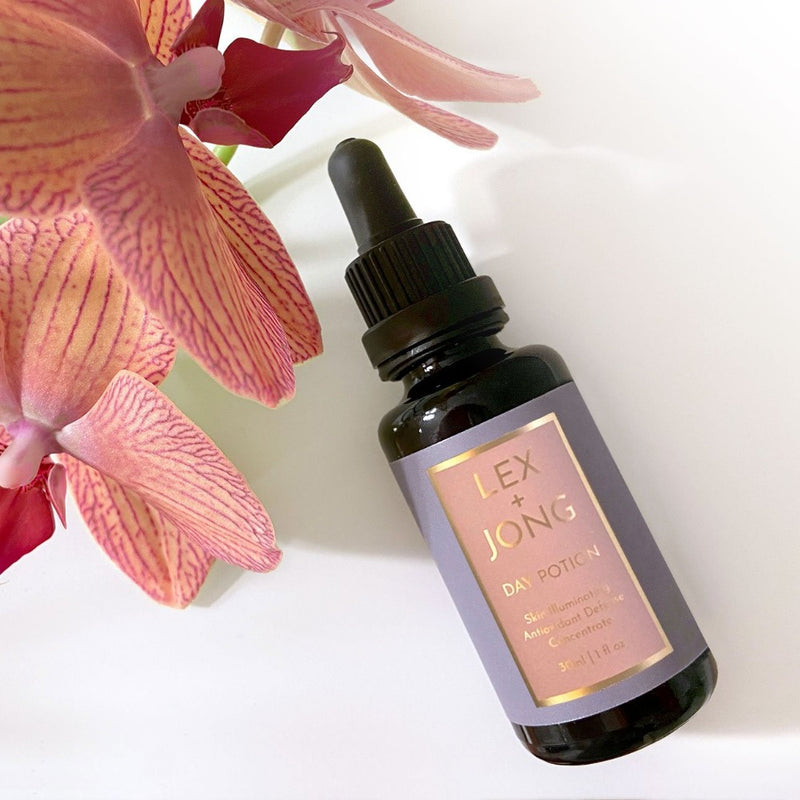 Day Potion (Skin Illuminationg Multi-vitamin Antioxidant Serum Concentrate) bottle - pictured with pink orchid -  helps seven the most ensitive skin thrive