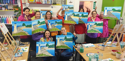 Paint Party group photo smiling painters holding up their paintings