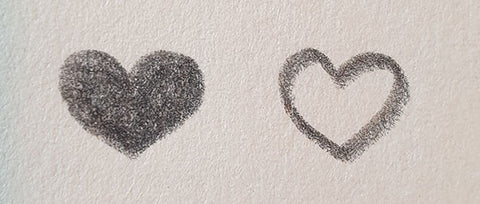 Two sketched hearts one outline and one shaded in