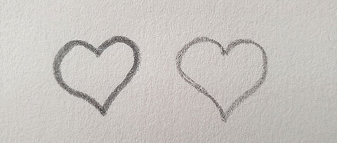 Two pencil sketched hearts one with a thicker line