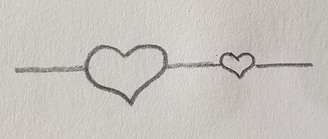 two hearts sketched in pencil one larger close up and one smaller in background