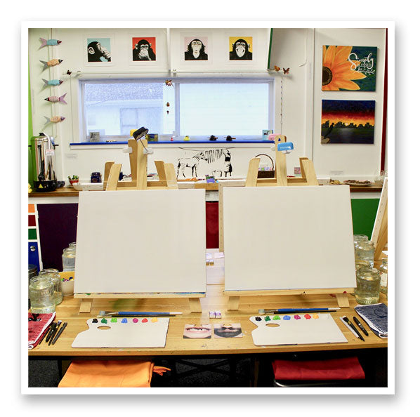 two easels with canvas paint on palettes and brushes ready for art classes wellington