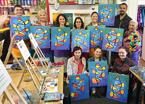 Smiling people holding up their finished paintings at team building paint party with Heart for Art