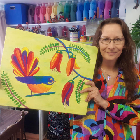 Silke holding brightly coloured Fantail painting with paint bottles behind