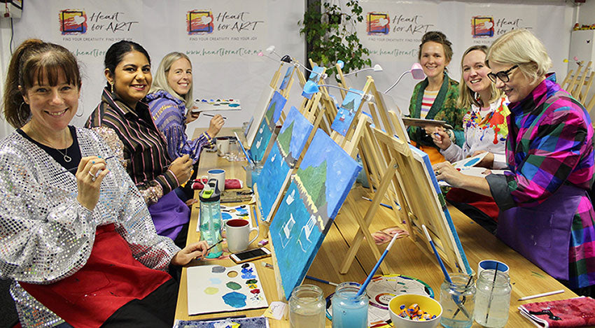 happy ladies in front of easels with brushes all art materials creating their island bay paintings