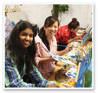 two women smiling holding paint palette and brush while painting in the Heart for Art studio Wellington