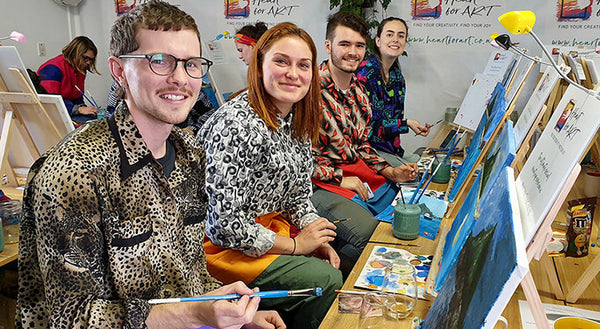 smiling people sitting in front of easels with paint palettes and brushes creating their paintings