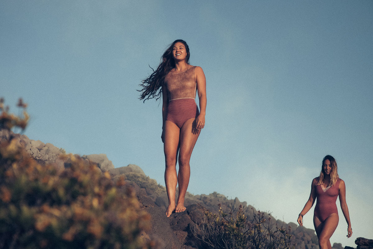 Rosie Jaffurs wears the Lido One-Piece. Sierra Lerback wears the Rhea One-Piece
