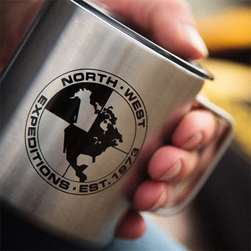 A hand holding North-West Expeditions Insulated Camp Mug with Lid and Black Logo