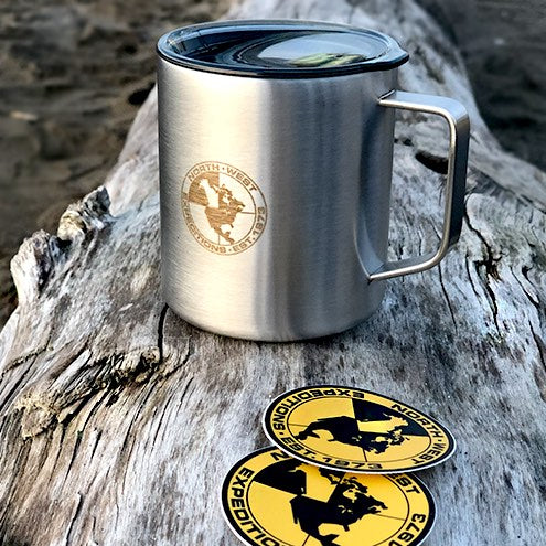 North-West Expeditions Insulated Camp Mug and lid engraved logo on log on beach log with stickers