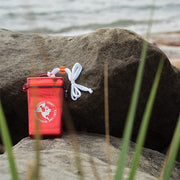 North-West Expeditions Float Kit (Floating First Aid Kit) on rocks with beach