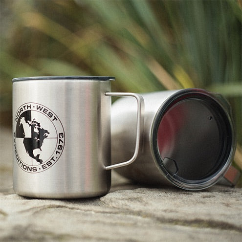 A pair of North-West Expeditions Insulated Camp Mugs on a beach rock