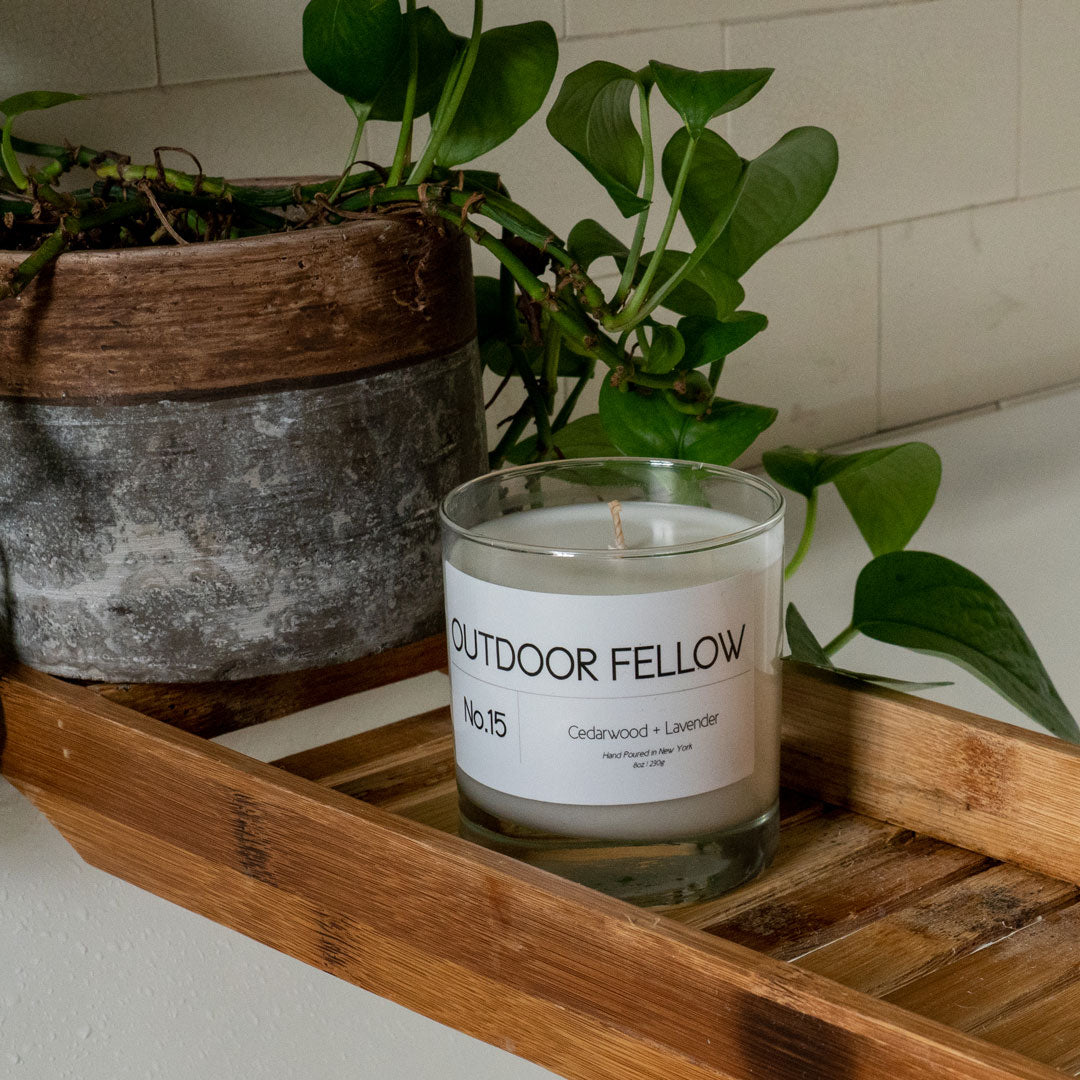 Outdoor Fellow scented candle on wooden bath shelf next to plant