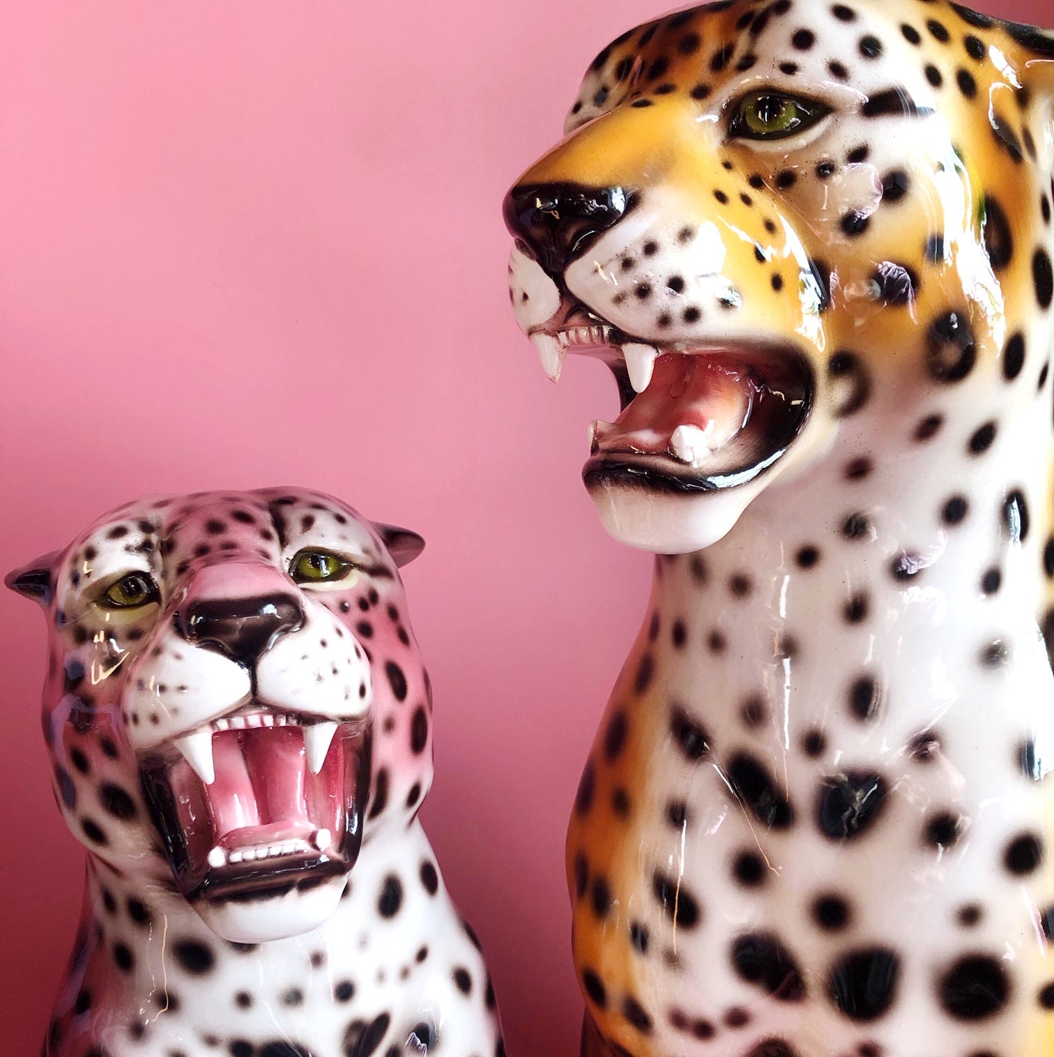 two ceramic leopards one pink, one orange against a pink background