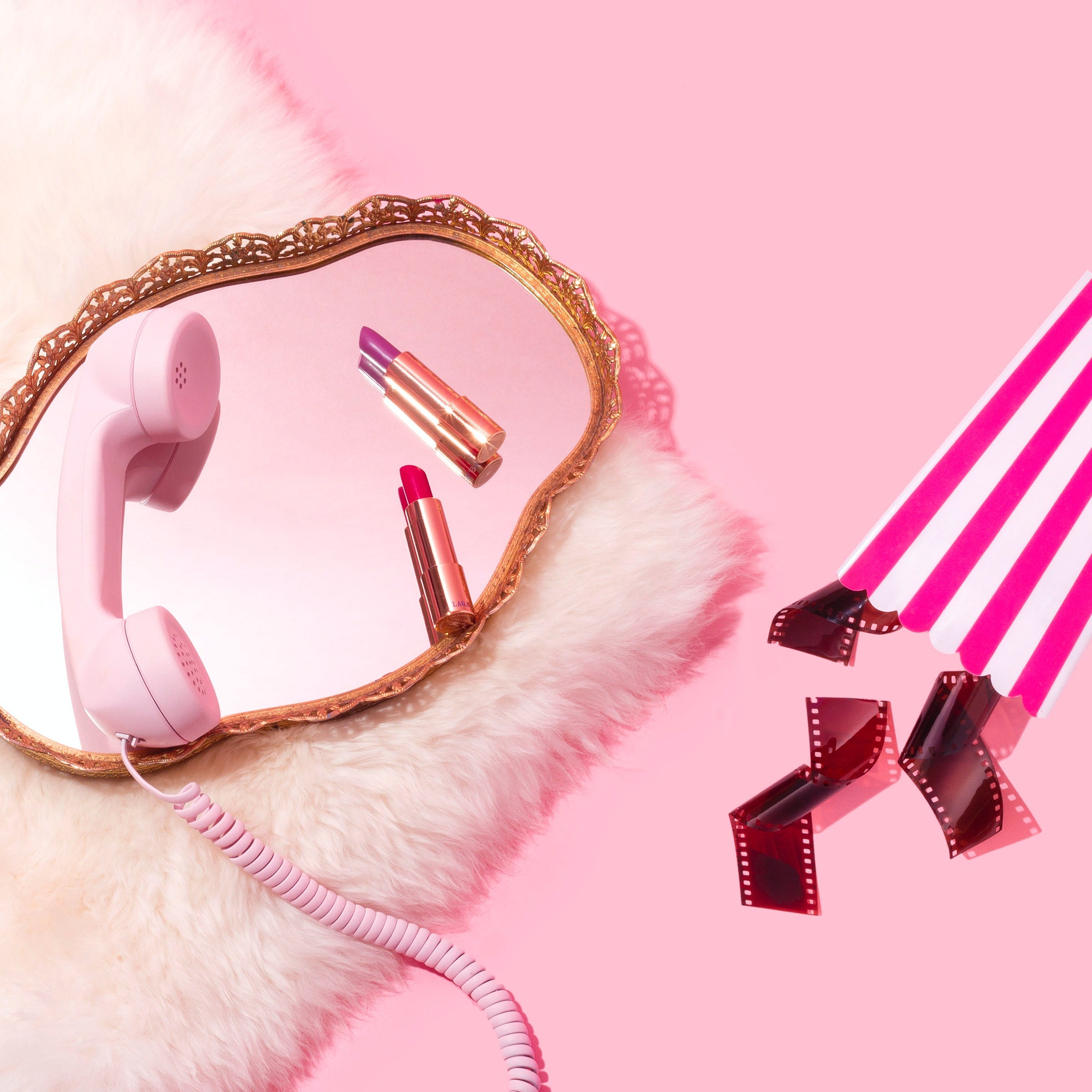 pink background with pink telephone and mirror flatlay