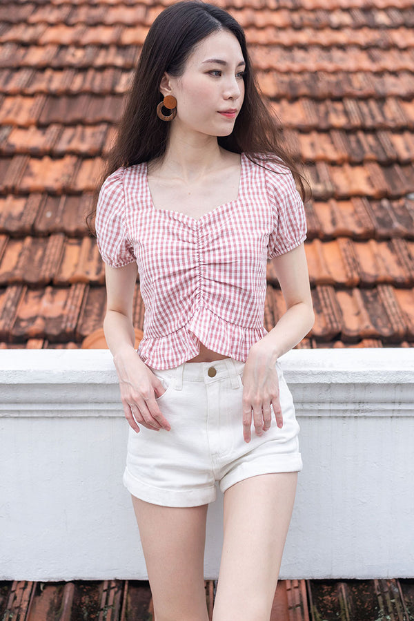 Desiree Gingham Ruched Peplum Top #MadeByDearLyla (Rose) l Dear Lyla Singapore l Shop Women Fashion Look preppy in this ruched top with sweetheart neckline which accentuates your bust and shows off your collarbones. Features slight puffy sleeves and a peplum fit that flatters your figure. Cut from lightweight and breathable cotton blend with the trendiest gingham prints. *Pair it with our Kayden Denim Shorts (White) to complete your look.