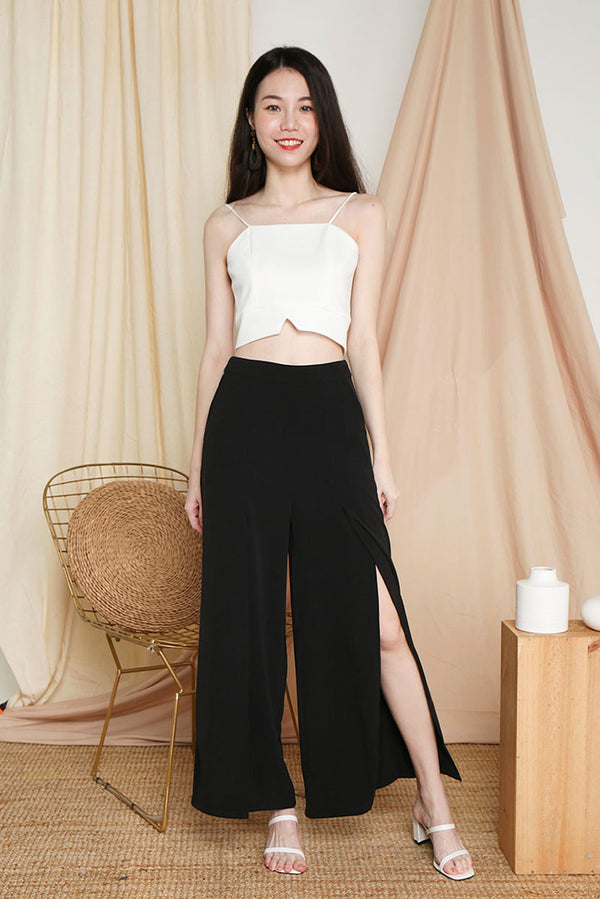 Mistletoe Flowy Slit Pants (Black) | Dear Lyla Singapore | Shop Women Fashion Online This flowy number looks stunning when you strut. Show off those beautiful legs of yours in subtle hints through the slits. We love how this pair of pants can bring you from work to party.  - Concealed back zip closure - Made of polyester - Functional side pockets  Available in Black and Rust.  Exclusively manufactured by Dear Lyla.  Pair with our Merry Fold Top or Gail Camisole Crop Top (White) to complete the look.