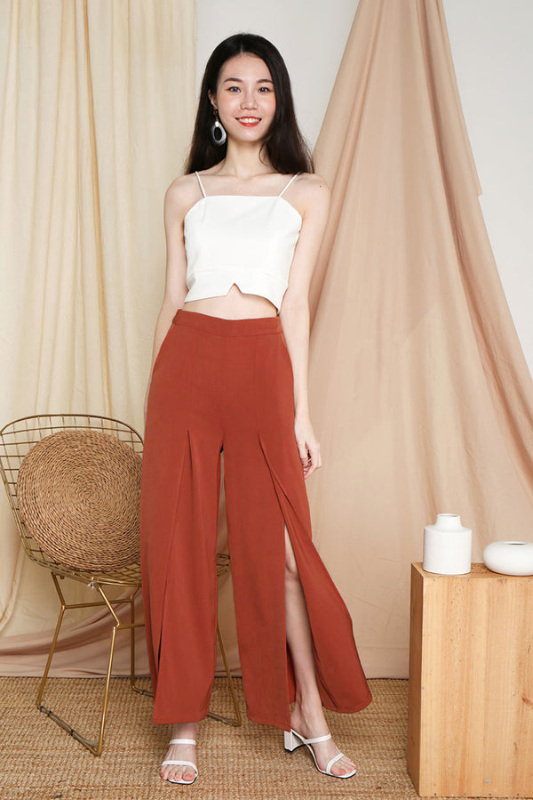 Mistletoe Flowy Slit Pants (Rust) | Dear Lyla Singapore | Shop Women Fashion Online This flowy number looks stunning when you strut. Show off those beautiful legs of yours in subtle hints through the slits. We love how this pair of pants can bring you from work to party.  - Concealed back zip closure - Made of polyester - Functional side pockets  Available in Black and Rust.  Exclusively manufactured by Dear Lyla.  Pair with our Merry Fold Top or Gail Camisole Crop Top (White) to complete the look.