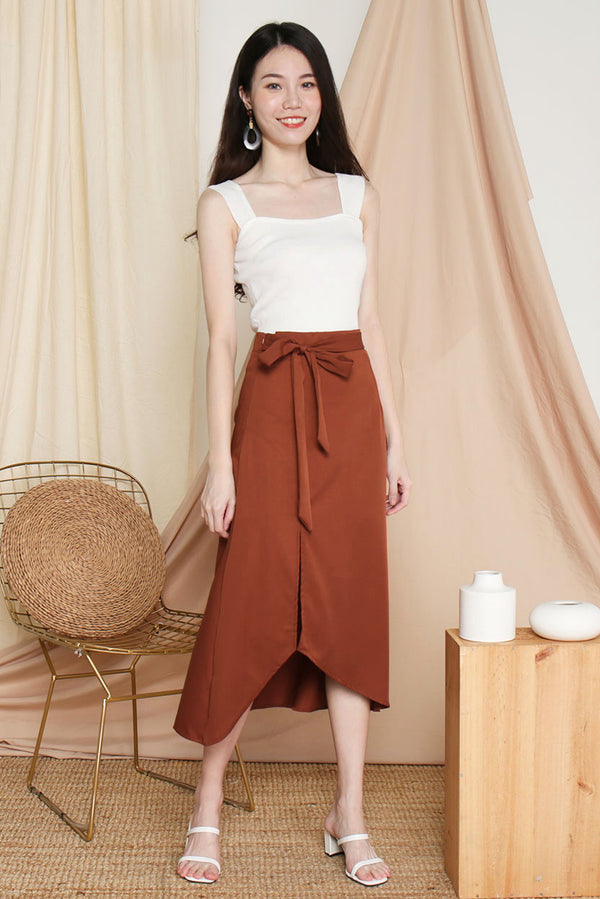 Victoria Tie-Waist Slit Midi Skirt (Rust) l Dear Lyla Singapore l Shop Women Fashion This romantic midi skirt elevates your look effortlessly. It comes with an attached tie-waist sash for an added touch of feminitely. Twirl gracefully in this lovely midi skirt which is suitable for all occasions.  - Concealed side zip closure - Attached tie-waist sash  - Non-lined, non-sheer - Made of polyester  Available in Rust and Black.  Pair it with our Gail Camisole Crop Top (Black) to complete the look.