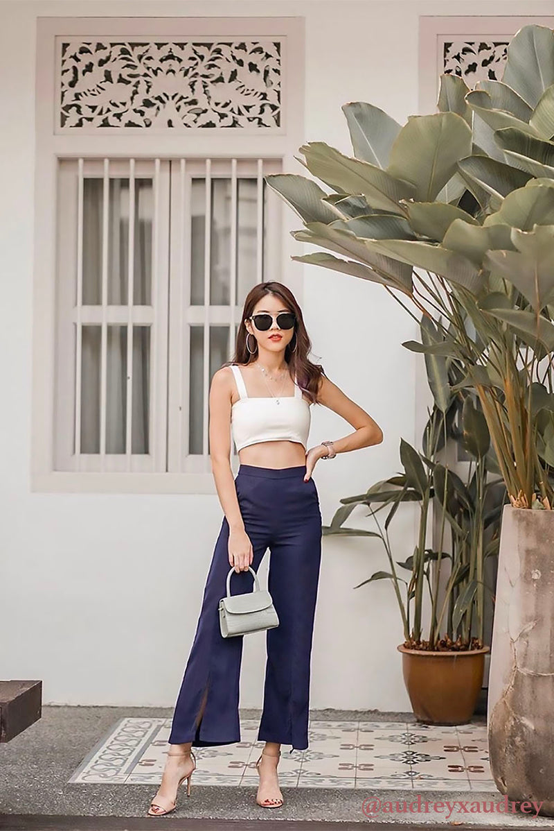 Delphin Wide Leg Slit Pants (Navy) l Dear Lyla Singapore l Shop Online Women Fashion Strut elegantly in this high-waisted flowy number which features a slit high detail. Perfect for that effortless chic look.  - Back zip closure  - Material is non-sheer - Made of polyester - Functional side pockets  Exclusively manufactured by Dear Lyla.  Pair with our Giselle Tie-Waist Crop Top to complete the look. Audrey lim audreyxaudrey