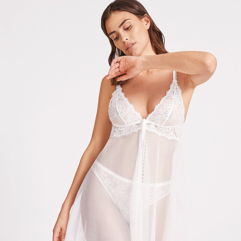 The Aubade Pour Toujours Bridal Babydoll seductively skims the body with draped voile that is open at the front. A small elasticated picot trim adds a vintage feel, whilst transparent tulle contrasts with romantic Cornely embroidery.