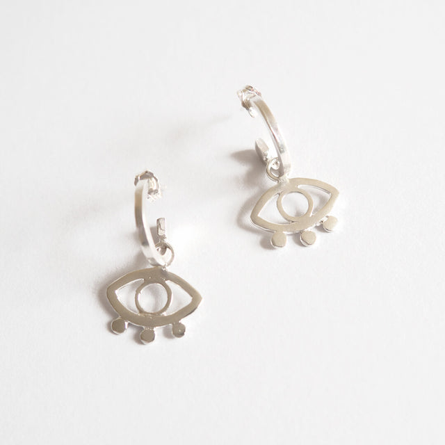 Close up of a pair of mini hoop ecosilver earrings with eye design.