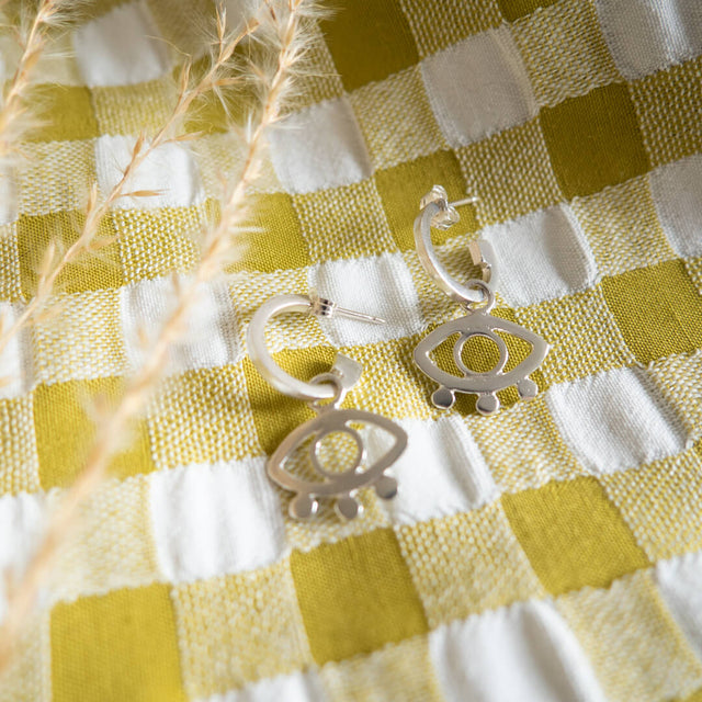 Handmade ecosilver eye hoop earrings on a gingham background.