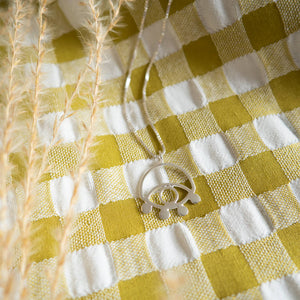 Close up of a handmade ecosilver eye necklace on a gingham background with dried flowers.