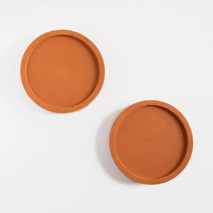 A pair of round coasters handmade using jesmonite in a terracotta colour by Klndra for Curious Makers