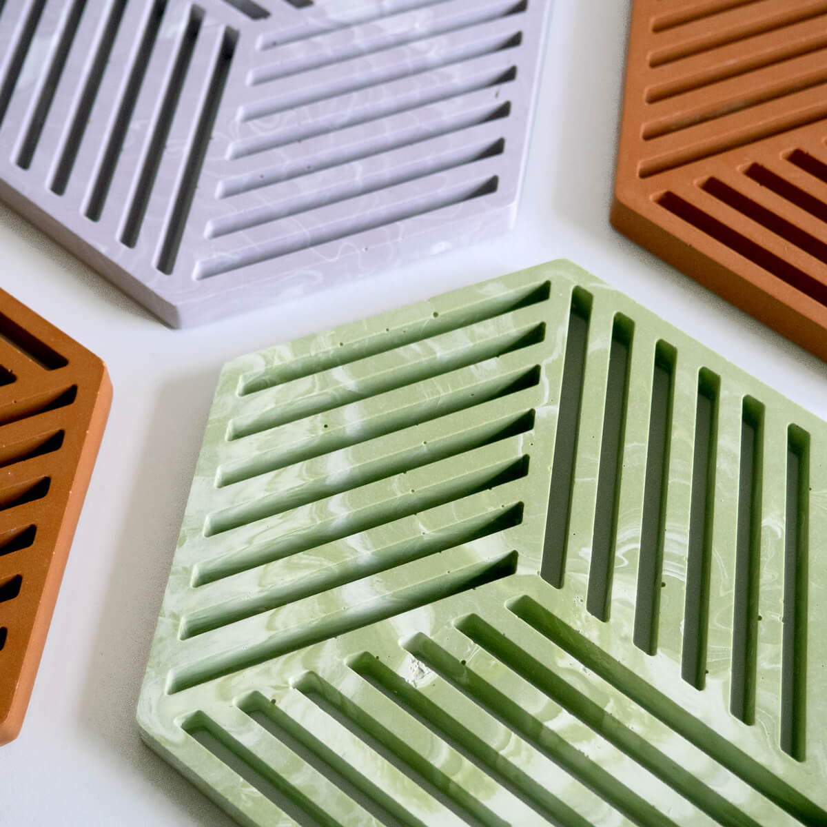 Geometric jesmonite trivets in sage green, lilac and terracotta by Klndra for Curious Makers