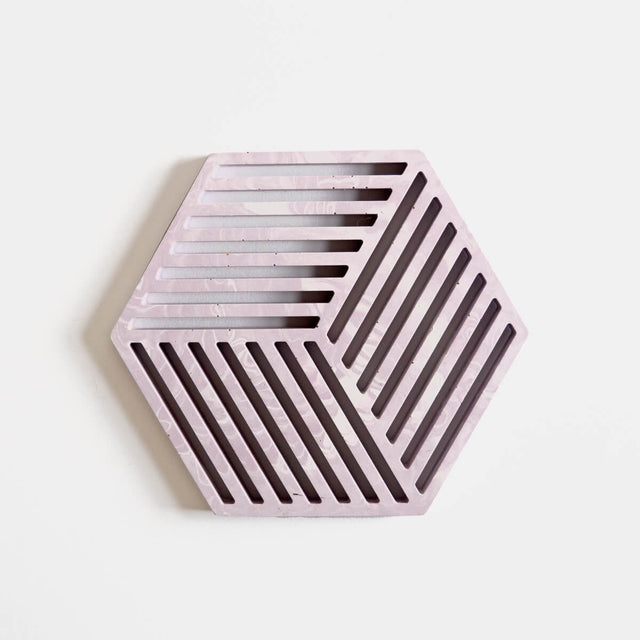 A hexagonal jesmonite trivet in cool lilac with a subtle marbled finish handmade by Klndra for Curious Makers
