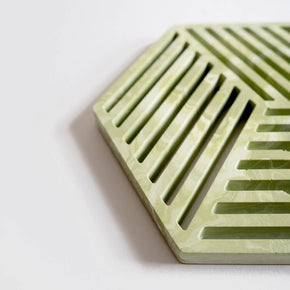 Detail of a contemporary sage green jesmonite hexagonal trivet with a subtle marbled finish by Klndra for Curious Makers