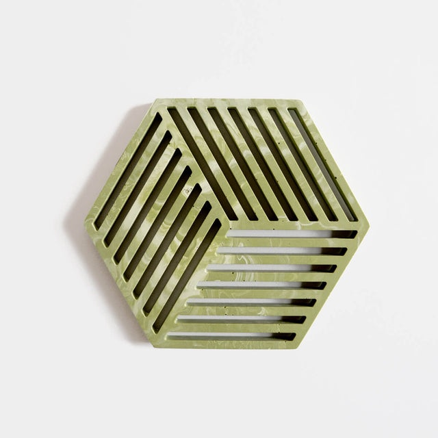 A contemporary sage green jesmonite hexagonal trivet with a subtle marbled finish by Klndra for Curious Makers