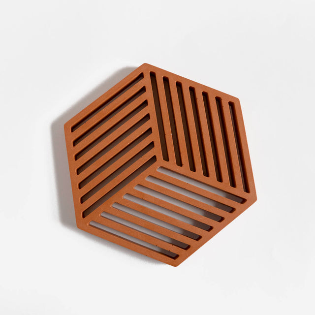 A contemporary hexagonal jesmonite trivet in a warm terracotta hue by Klndra for Curious Makers