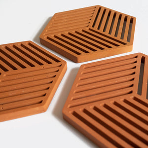 Detail of three hexagonal trivets in a warm terracotta tone by Klndra for Curious Makers
