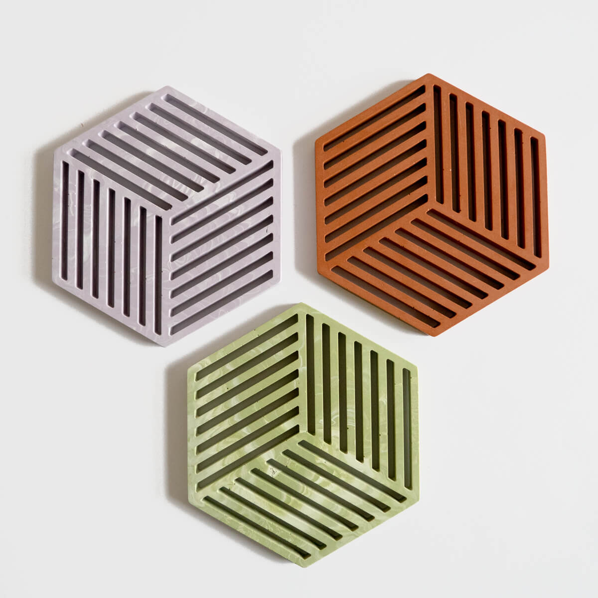 A group of 3 hexagonal jesmonite trivets in lilac, sage and terracotta handmade by Klndra for Curious Makers.