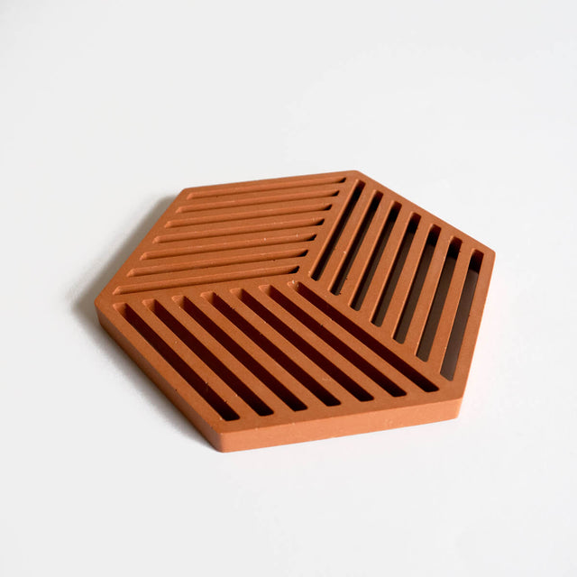 A contemporary jesmonite hexagonal trivet in a warm terracotta hue by Klndra for Curious Makers