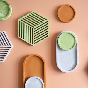 A group of handmade jesmonite coasters, trivets and trays in lilac,  sage and terracotta.
