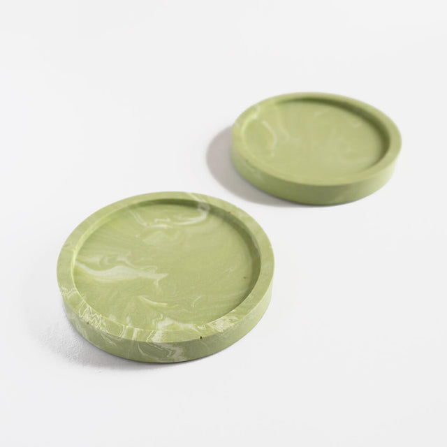 A pair of handmade round coasters with a sage green marbled pattern by Klndra for Curious Makers