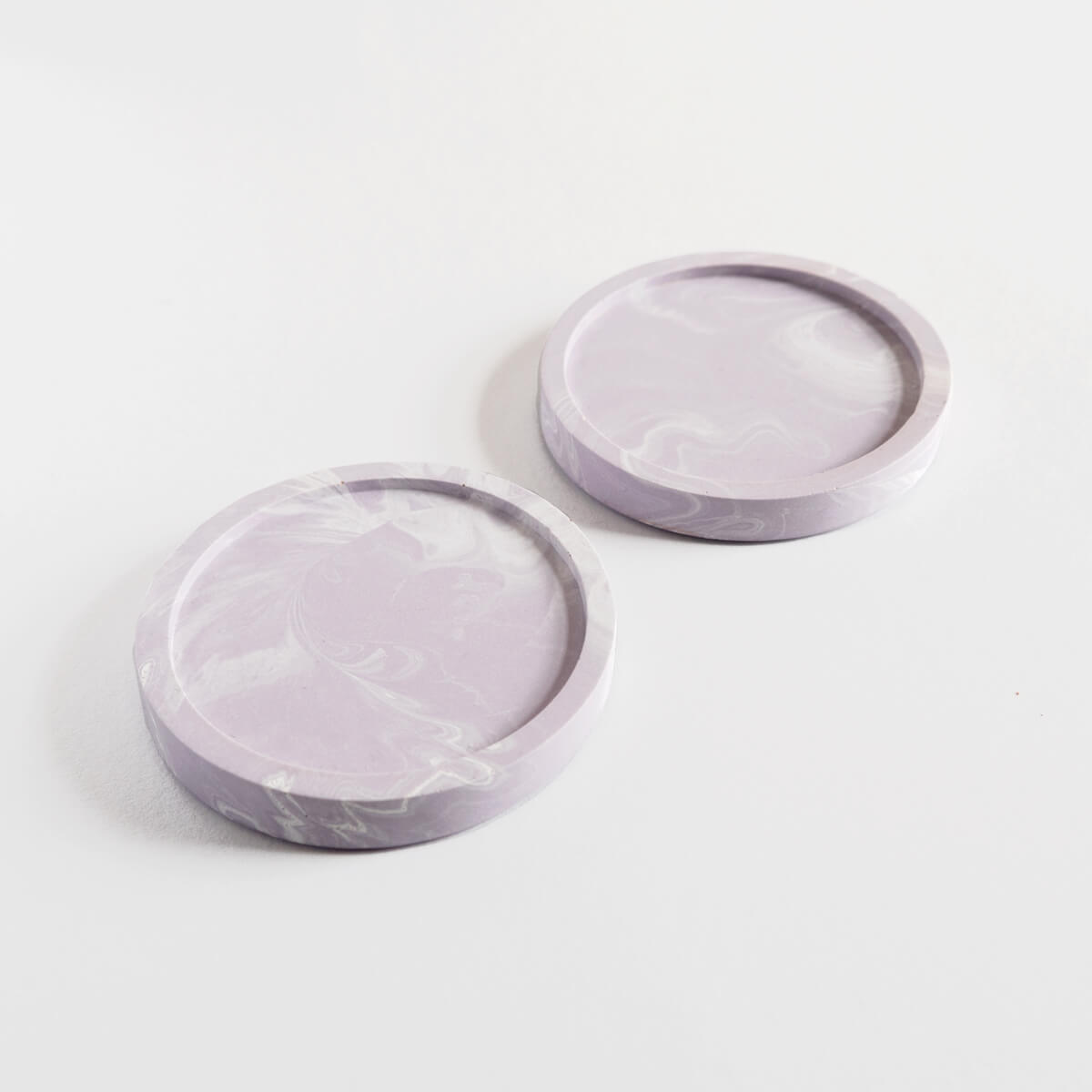 A pair of marbled lilac round coasters handmade by Klndra for Curious Makers