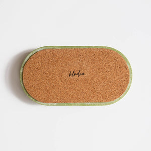 The back of a marbled sage green jesmonite tray by Klndra for Curious Makers showing the cork base to protect surfaces.