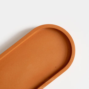 A close up of  a jesmonite oval tray in a warm terracotta hue handmade by Klndra for Curious Makers