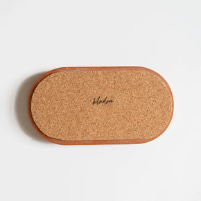 The back of  a terracotta jesmonite oval tray showing the cork base that protects your surfaces. Handmade by Klndra for Curious Makers