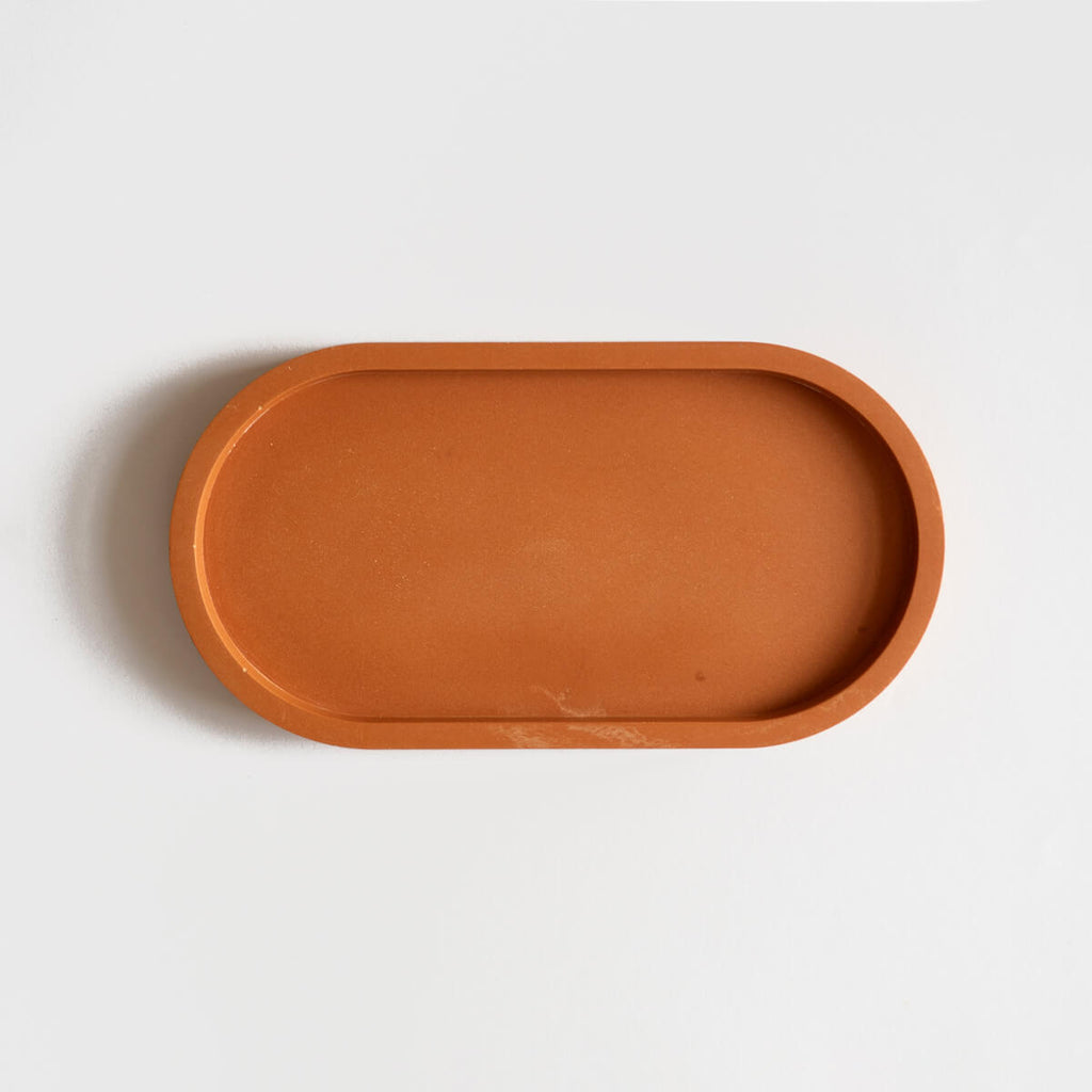 A jesmonite oval tray in a warm terracotta hue handmade by Klndra for Curious Makers