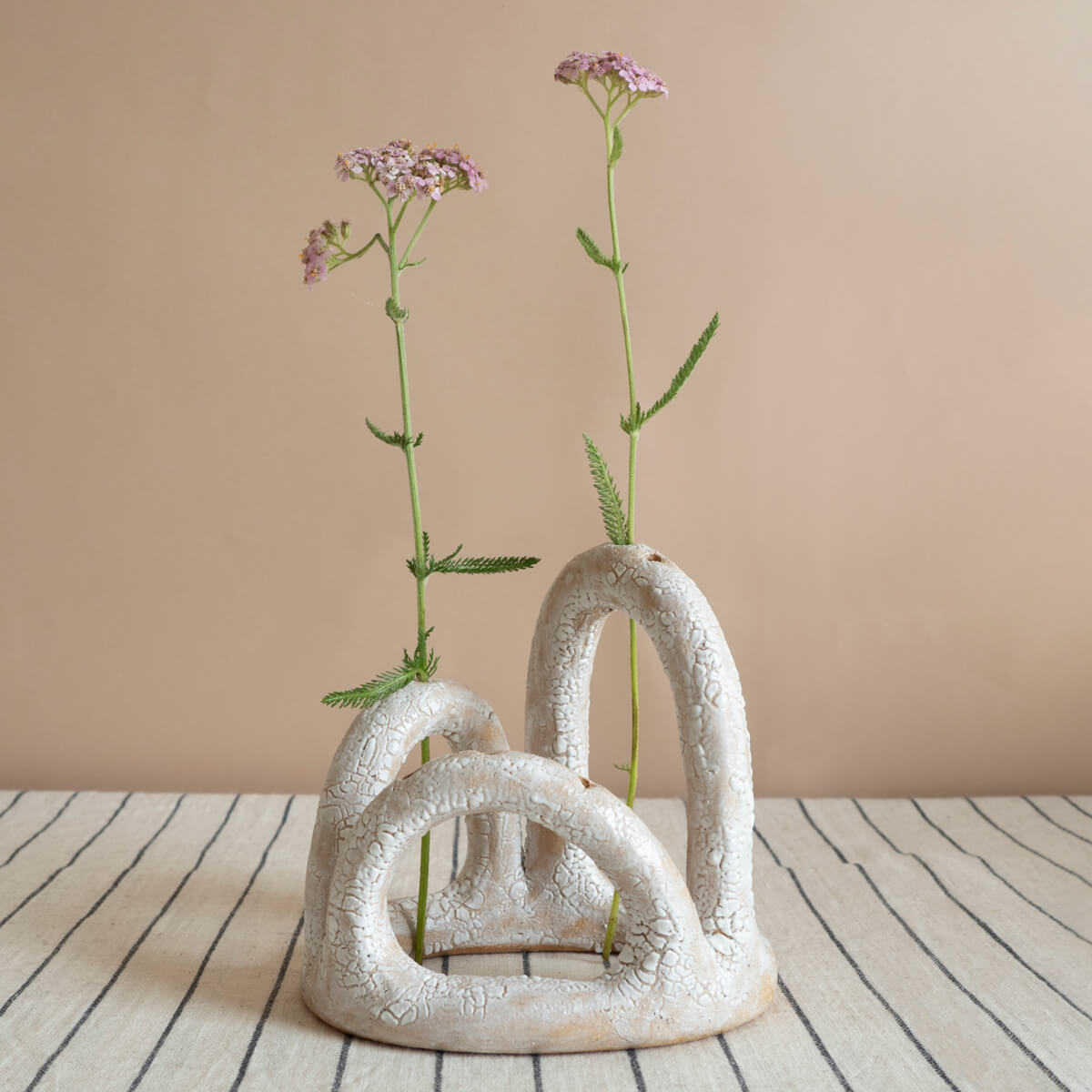 Bud vase with delicate flowers on a striped tablecloth, handmade by Manifesto for Curious Makers