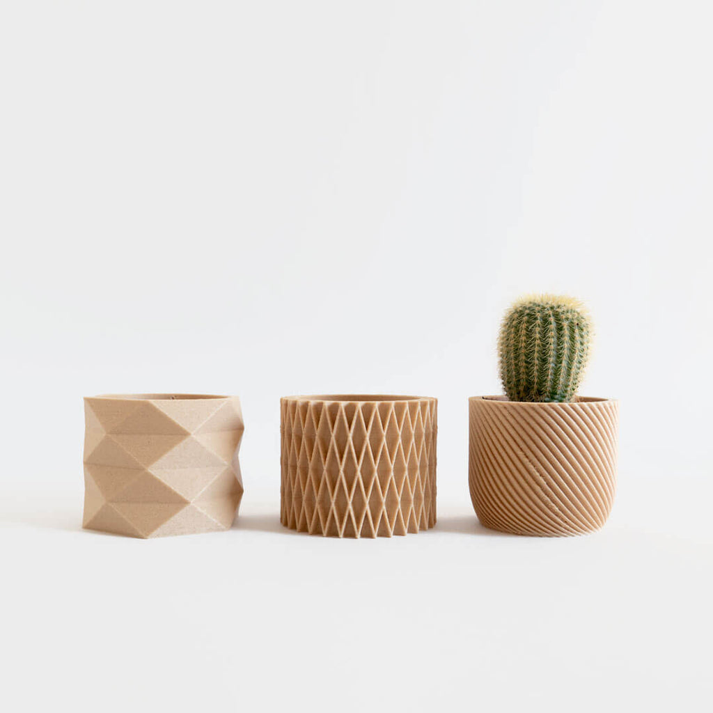 Three mini 3d printed planters with different geometric diamond designs.