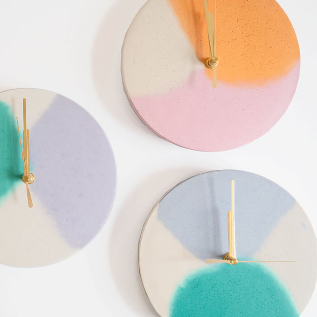 A group of round concrete wall clocks by Studio Emma for Curious Makers