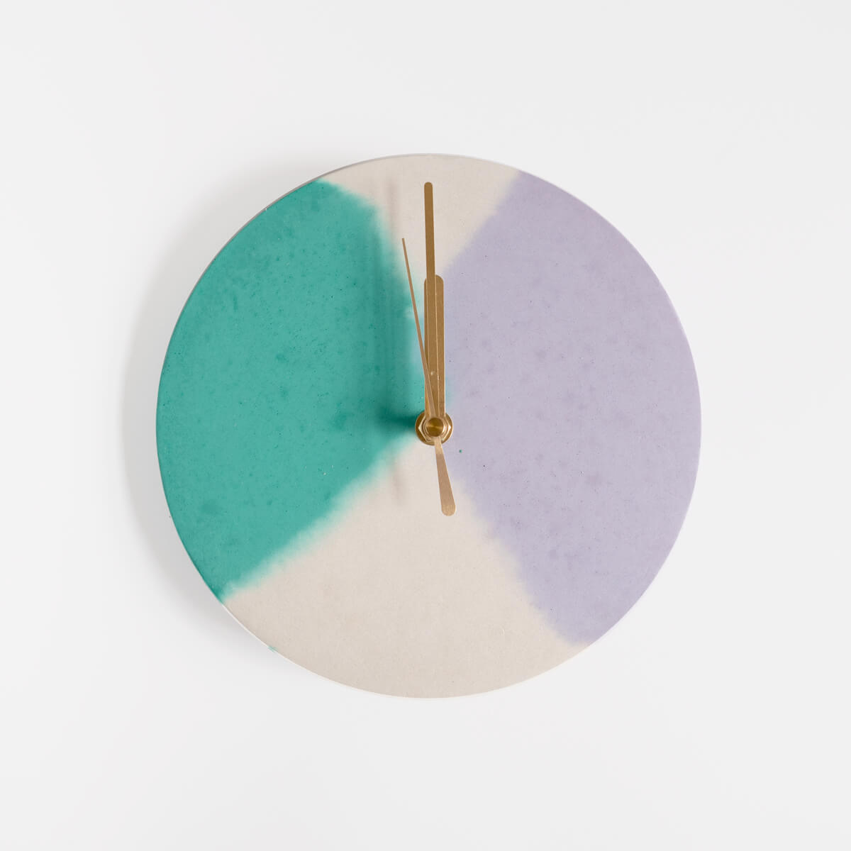Round concrete wall clock with a sage and lilac pattern by Studio Emma for Curious Makers